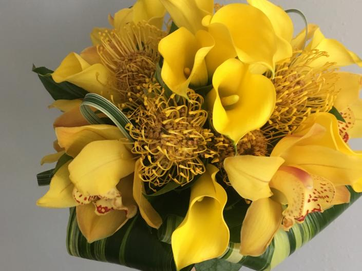 [Image: Stand out on your big day with this brides bouquet filled with Yellow calla lillys, yellow protea pincushions, and yellow cymbidium orchids.]