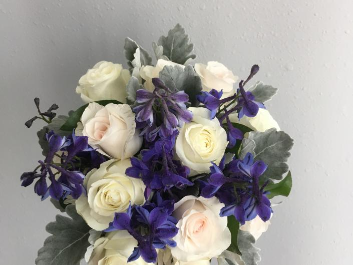 [Image: Bride or Bridesmaid Bouquet using dark blue delphinium, blush and ivory roses, accented with dusty miller.]