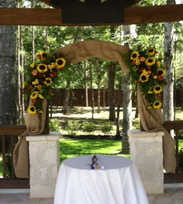 [Image: Burlap arch,accented with sunflowers, roses, and viking poms]