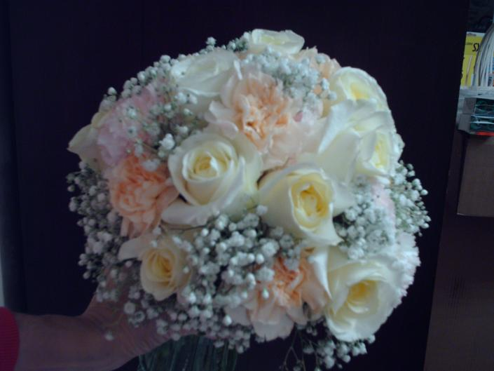 Peach and pale pink carnations, creme roses, and baby's breath