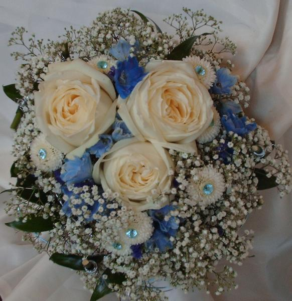 Creme roses, blue delphinium, white button mums and baby's breath, nestled in a blue and silver wire nest, accented with blue jewels and greenery]