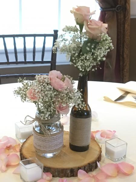 [Image: Mason jar, beer bottle with twine, baby's breath and light pink roses]