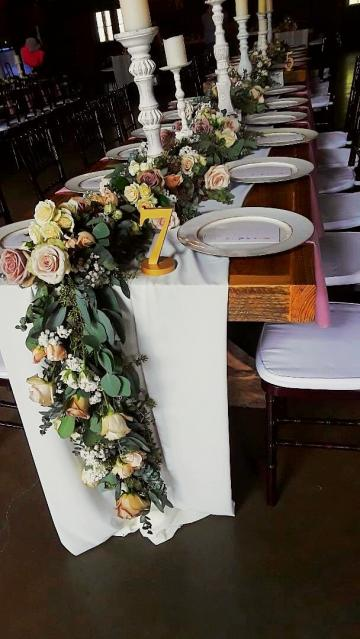 Luxurious table runner full of roses, spray roses, and babies breath.