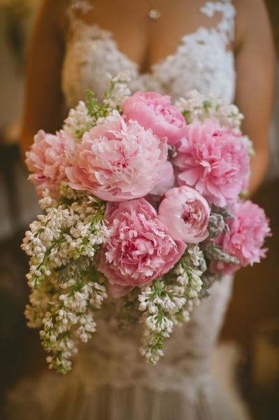 [Image: A spring bouquet featuring pale pink peony's, white lilac and dusty miller greenery]