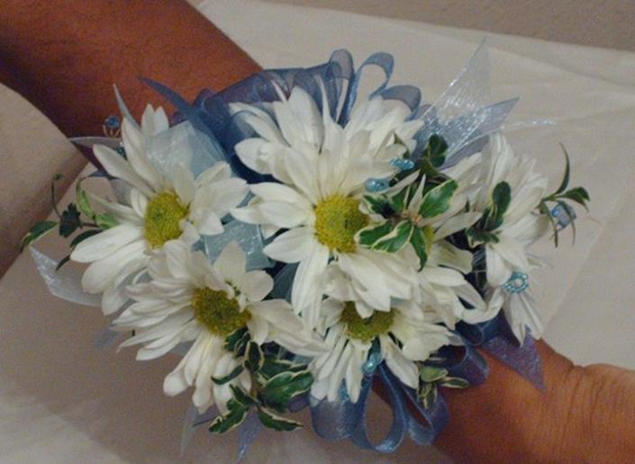 [Image: A simple corsage made of white daisies, greenery, and blue ribbon]
