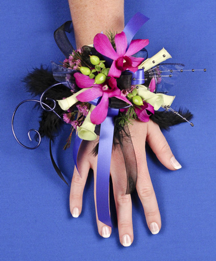 [Image: This prom corsage is so fun with the purple flowers, ribbon, wire and feathers.]